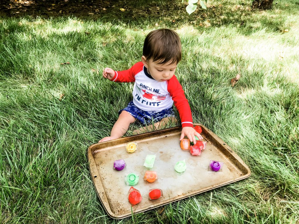 Try this quick and simple frozen toy ice cube activity for your baby. If you need an outdoor activity to help your baby cool off in the summertime and stay busy, this is it. The coldness of the ice cubes will be fun for your baby to nibble on and play with. This activity promotes fine motor skills and fun sensory play. Outdoor sensory baby activity.