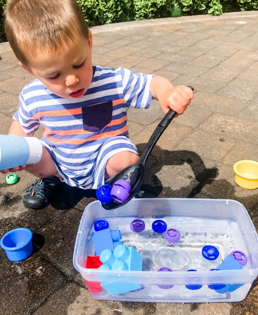 A simple sensory outdoor activity for your toddlers or babies. Use a spoon to scoop small toys out of a container of water for fun outside play.